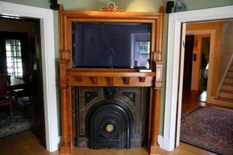 The centerpiece of the spacious living room is an oak fireplace mantel which the original mirror has been deftly replaced with a flat-screen television.